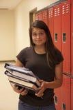 Female student holding textbooks. A female student poses while holding textbooks and notes by her school locker Stock Photos