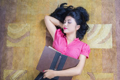 Female student holds book and sleeping on carpet. Image of beautiful female student holding a textbook and sleeping on the carpet at home Royalty Free Stock Photography