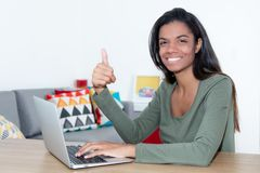 Female student at home with laptop showing thumb up. Female student at home at desktop with laptop showing thumb up Royalty Free Stock Photo