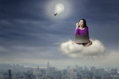 Female student with laptop on the cloud Stock Photos