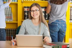 Female Student With Laptop Sitting At Table In. Portrait of happy female student with laptop sitting at table in college library Royalty Free Stock Image