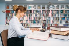 Female student at the laptop in university library. Young woman in reading room, knowledge depository royalty free stock image