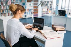 Female student at the laptop in university library. Young woman in reading room, knowledge depository royalty free stock images