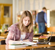 Female student with laptop working in library Stock Photos