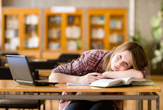 Female student with laptop working in library.  Royalty Free Stock Image