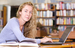 Female student with laptop working in library. Looking at camera Stock Photos