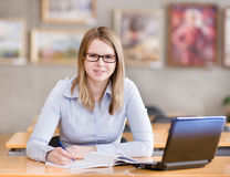Female student with laptop working in library. Royalty Free Stock Photo