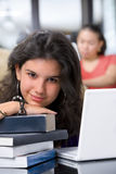 Female student leaning on books' pile Royalty Free Stock Photography