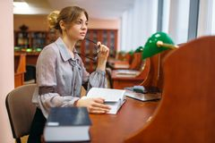 Female student learning book in university library. Woman studying in knowledge depository, education royalty free stock photos