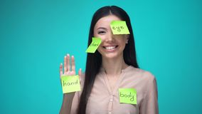 Female student learning English, covered with body parts sticky notes, education