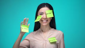 Female student learning French, covered with body parts sticky notes, education