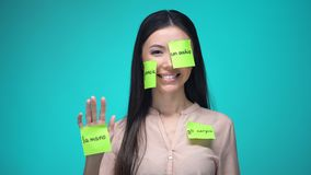 Female student learning Italian, covered with body parts sticky notes, education