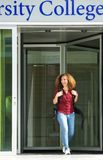 Female student leaving college building. Portrait of a young female student leaving college building Royalty Free Stock Photography