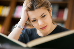 Female student in a library absorbed in study Stock Image
