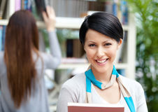 Female student at the library against bookshelves Stock Image
