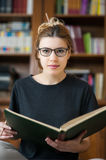 Female student in a library looking at camera. Young female student portrait looking at camera while holding a book in library, bookcase in background Royalty Free Stock Images