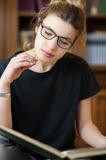 Female student in a library reading a book. Young female student working in library, focused on book, bookcase in background Royalty Free Stock Image