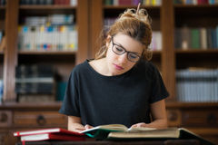 Female student in a library reading on a desktop. Young female student reading in library, with dektop and books, bookcase in background Stock Images