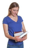 Female student with long blonde hair looking at a book Stock Photos