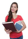 Female student with long dark hair looking at a book Stock Image