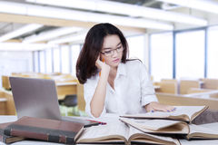 Female student with long hair reading books in class Stock Images