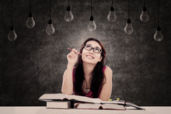 Female student looking at light bulbs Royalty Free Stock Photo