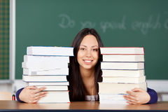 Female student looking between stacked books Stock Photo