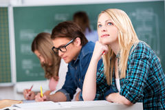 Female Student Looking Up While Sitting With Classmates At Desk. Thoughtful young female student looking up while sitting with classmates at classroom desk Stock Image