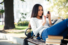 Female student lying on the bench and using smartphone Royalty Free Stock Photography