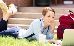 Female student lying down on lawn grass working on laptop. College female student lying down on lawn grass working on laptop at university campus outside on Stock Image