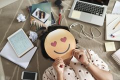 Fake emotion logo. Female student lying on floor and covering behind paper face with heart eyes stock photography