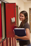 A female student opens a locker. A female student smiles while opening her locker Stock Photography