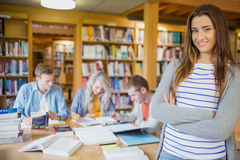 Female student with others in background at library Royalty Free Stock Photos