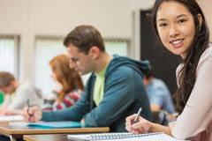 Female student with others writing notes in classroom Royalty Free Stock Photography