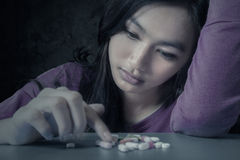 Female student with pills. Portrait of teenge girl choosing pills with stressful expression, symbolizing a drugs addict Royalty Free Stock Photo