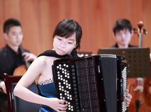 Female student playing accordion Stock Photo