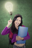 Female student pointing at a bright bulb Royalty Free Stock Image