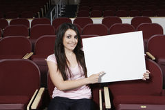 Female Student Pointing Towards Sign Board In Classroom Royalty Free Stock Images