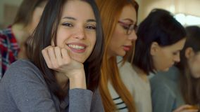 Female student poses at the lecture hall. Young female student posing at the lecture hall. Close up of attractive brunette girl looking into the camera at the Stock Image
