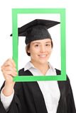Female student posing behind a green picture frame Stock Images
