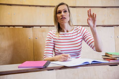 Female student raising a hand in class Stock Images