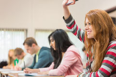 Female student raising hand by others in classroom Royalty Free Stock Photography