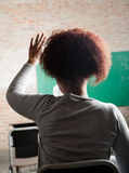 Female Student Raising Hand To Answer In Classroom. Rear view of young female student raising hand to answer in classroom Royalty Free Stock Photography