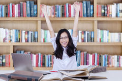 Female student raising hands in library while studying Royalty Free Stock Photo