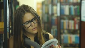 Female student read book in library with bookshelf as background. A female college student studies in the library, girl reading a book in the library stock video footage