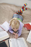 Female Student Reading In Bed. Full length of young female student reading in bed Royalty Free Stock Images