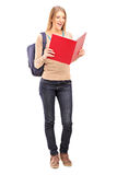 Female student reading a book. Full length portrait of a female student reading a book  against white background Royalty Free Stock Photography