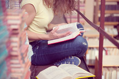 Female student reading book. S in library Royalty Free Stock Photos