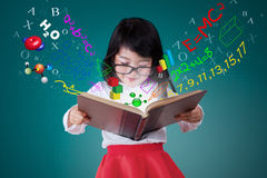 Female student reading book with formula. Female elementary school student reading a book with formula of math Stock Images