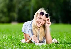 Female student reading book on the grass Stock Images
